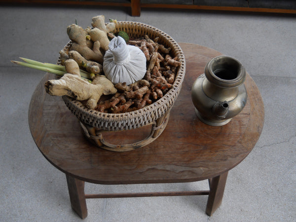 Wooden table with wooden baskets on top, full of herbs used in Thai herbal medicine: lemongrass, Thai ginger, kaffir lime; and a white cotton herbal compress massage ball.