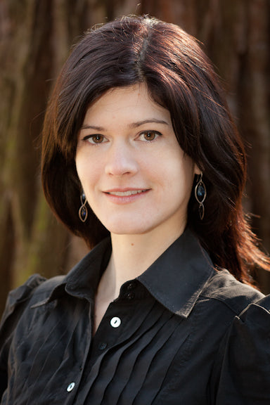 Photograph of Beth Russell, a white woman with brown hair and eyes, in a black collared shirt, smiling.