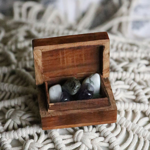 A tiny wooden box with tumbled Amethyst, Labradorite, and Moonstone inside