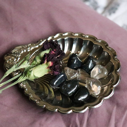 A Silver Dish with Tumbled Black Onyx and Smokey Quartz on it