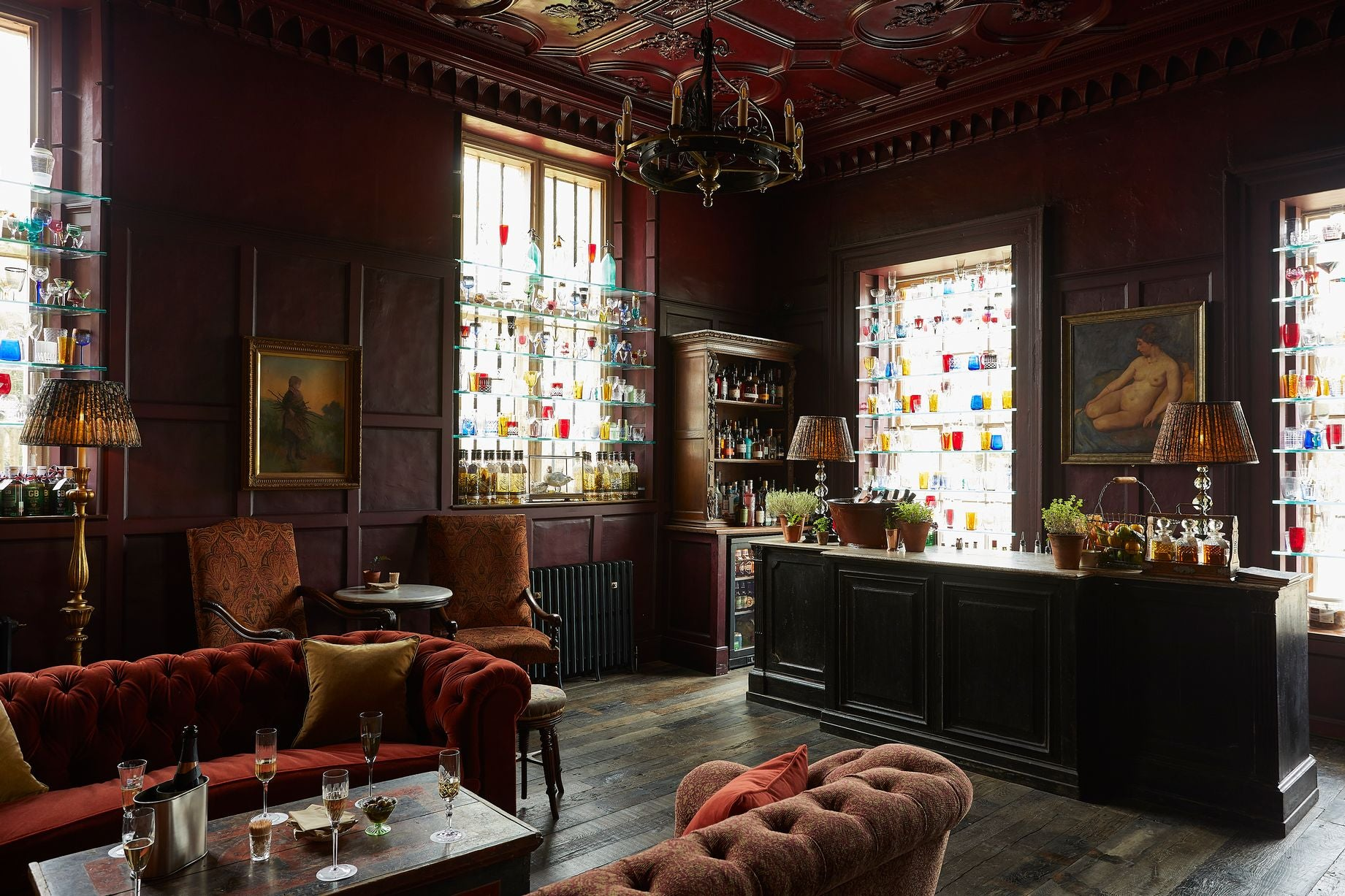 The inside of The Pig hotel bar with dark wooden interior, a chandelier and chesterfield sofas.