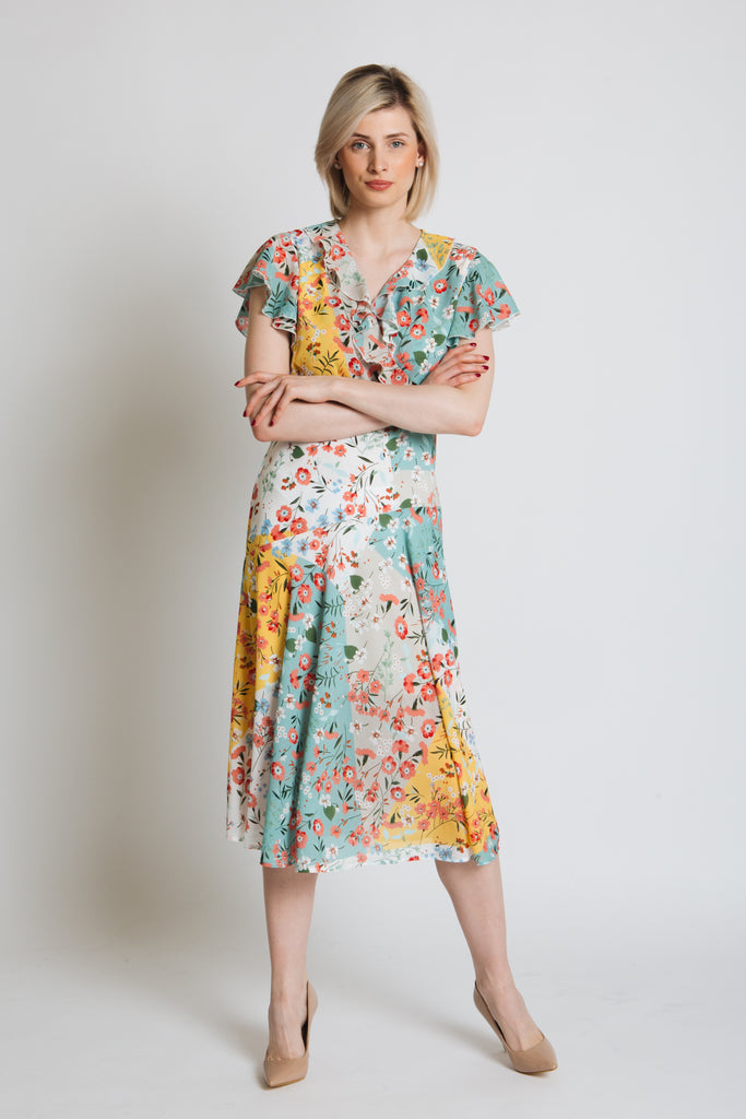 Patchwork floral print dress with bias panels. Cross over top with ruffle, flared sleeve. Fitted at waist with invisible zip.