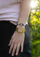 Daybreak - Single - Season two Palm anchor bracelet with pink and blue nylon band. On girl models arm.