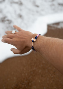 Daybreak - Single - Season two Palm anchor bracelet with pink and blue nylon band. On models hand on beach.
