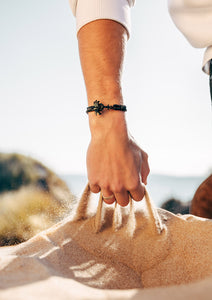 Eclipse - Season two Palm anchor bracelet with black leather. On the beach.