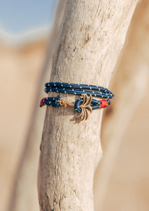 Seven Seas - Triple - Season two Palm anchor bracelet with blue and white nylon band. Close up outside.