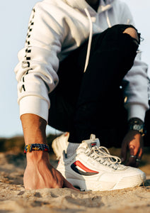 Seven Seas - Triple - Season two Palm anchor bracelet with blue and white nylon band. On male model on the beach.