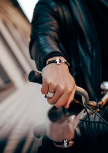 Starlight - Season two Palm anchor bracelet with black leather. On model on a bike.