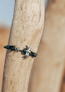 Starlight - Season two Palm anchor bracelet with black leather. Close up outside.