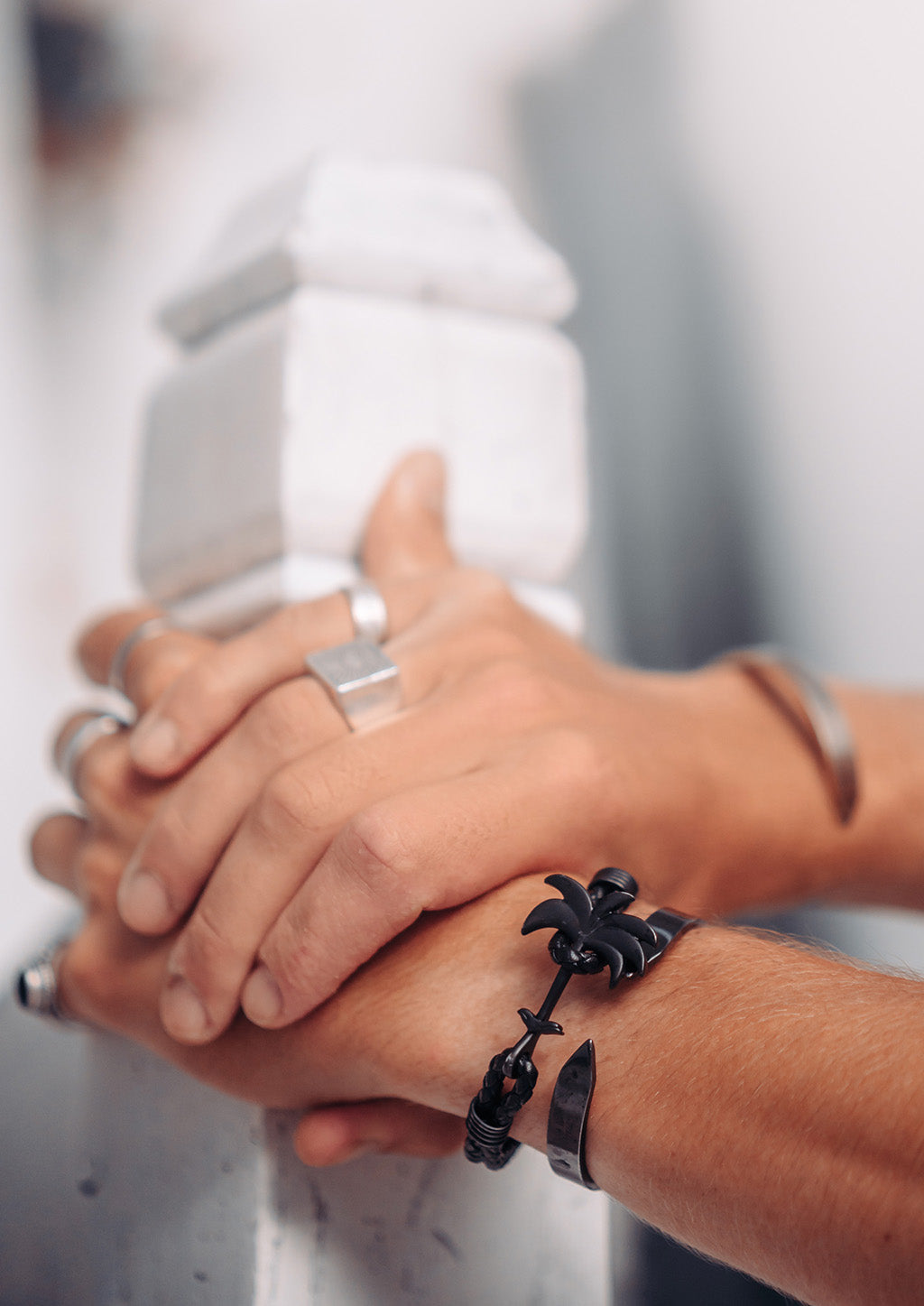 Pitch Black - Palm anchor bracelet with black leather. Lifestyle photo holding hands.