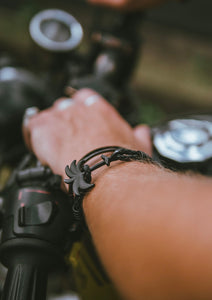 Pitch Black - Palm anchor bracelet with black leather. Lifestyle photo on motorcycle.