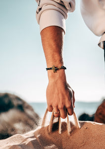 Trophy - Single - Season two Palm anchor bracelet with black and white nylon band. On male model on the beach.