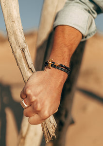 Trophy - Triple - Season two Palm anchor bracelet with black and white nylon band. On male model on the beach.