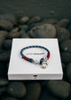 Voyager - Single - Season two Palm anchor bracelet with blue and red nylon band. On palm band box.
