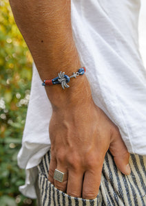 Voyager - Single - Season two Palm anchor bracelet with blue and red nylon band. On male model.