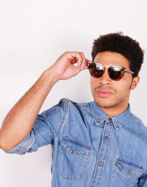 Black guy in Denim shirt wearing brown goali sunglasses