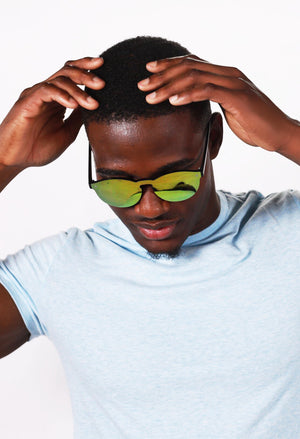 Black man with hands on head wearing gold Omare shades