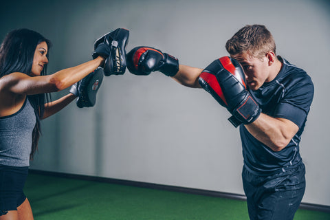 Man boxing/hitting mitts with women partner
