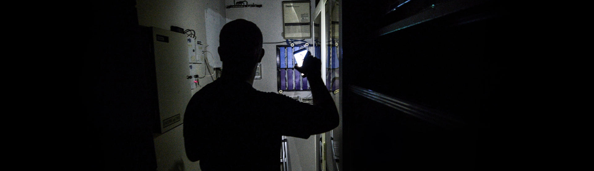 A man navigating a dark hallway with phone flashlight, looking for the fuse box.
