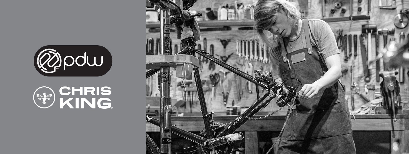 Bike mechanic working on a rear derailleur, and the PDW and Chris King logos.