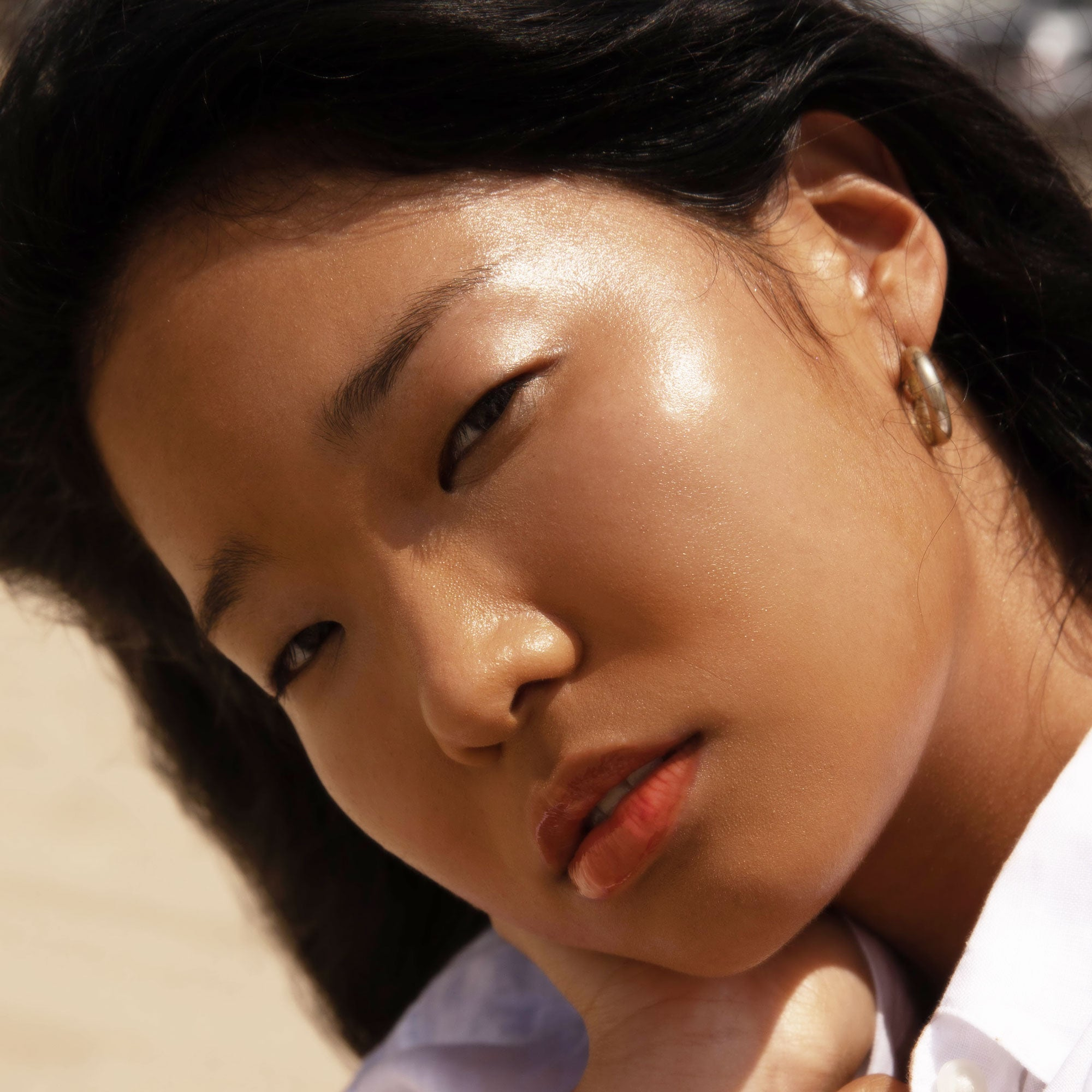 Closeup shot of girl with dewy cheeks wearing SuperDew Shimmer-Free Highlighter Balm by Tower28 Beauty