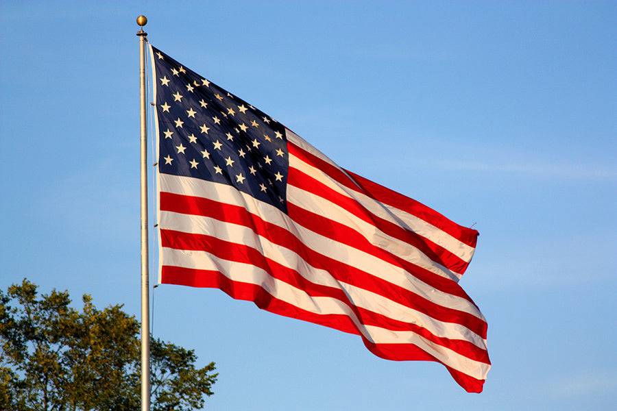 american flag in the wind blue sky