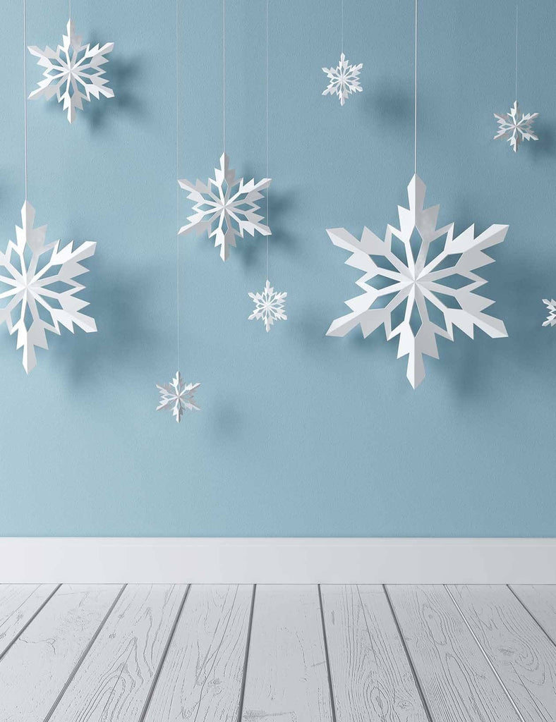 Snowflake Paper Cutting Hanging Before Blue Wall Backdrop