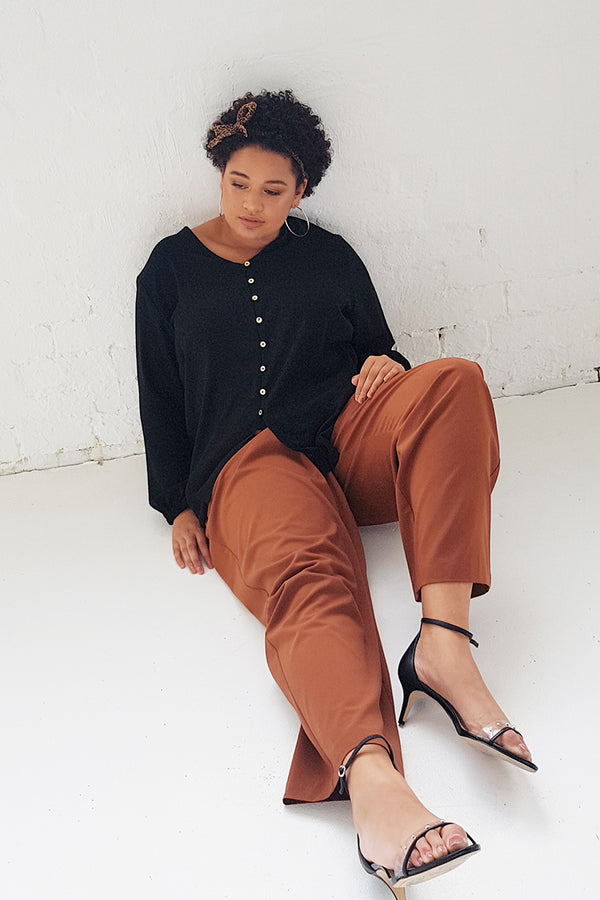 Our size 16 model Brie is sitting on the floor wearing the black Marly shirt teamed with the tobacco Penny pant. She has accessorised with large gold hoop earrings & an animal print scarf tied around her hair.