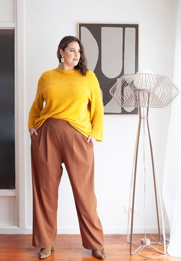Amelia is standing up with her hands in the pockets of the new tobacco pull on pallazo pant. She has teamed it with the honeycomb colour crew neck jumper and has a small section of the front of the jumper tucked into the front pant waistband.  She has accessorised this outfit  with animal print ankle boots & chunky gold earrings.  Amelia is standing next to a tall metal floor lamp  in front of a geometric black & white artwork hanging on the white wall.