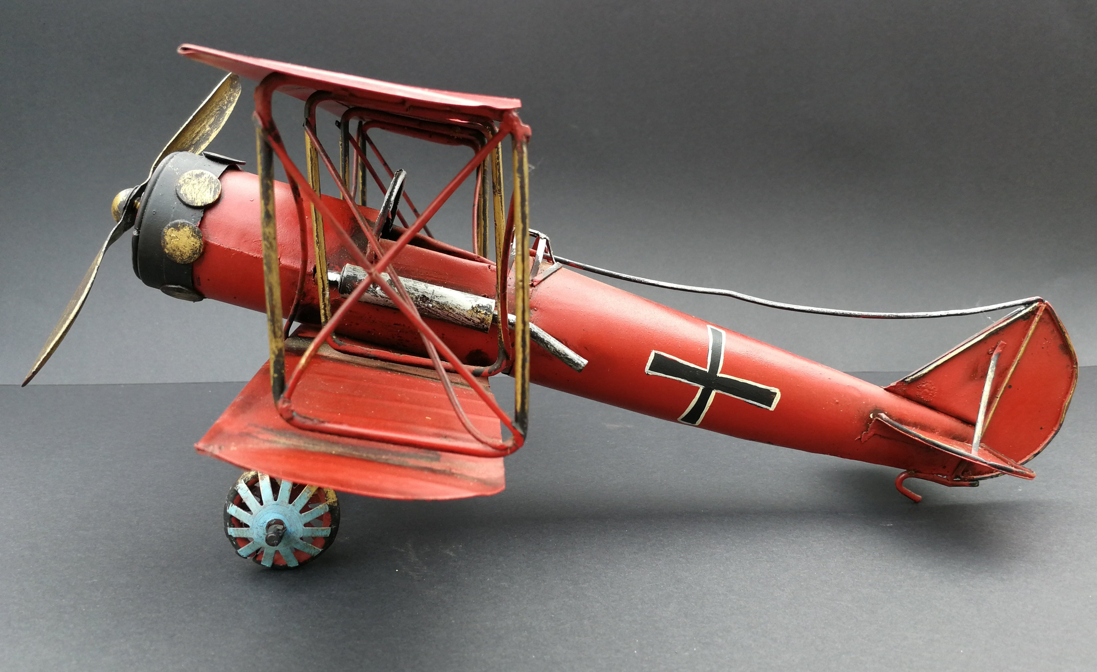 Tin aeroplane. Red and black. Hand made. Side view.