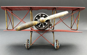 Tin aeroplane. Red and black. Hand made. Front view.