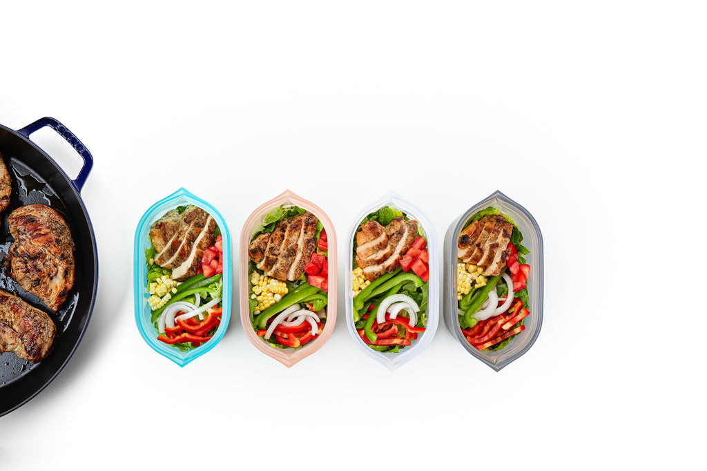 Reusable silicone dishes with fajita chicken salad on white smaller pan