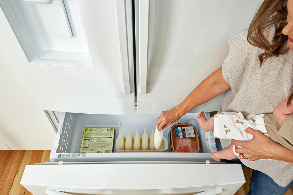 Reusable breastmilk bag set in freezer with mom reaching in while holding baby