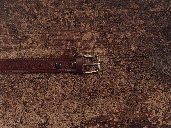 brown belt with celtic knot design and brass buckle