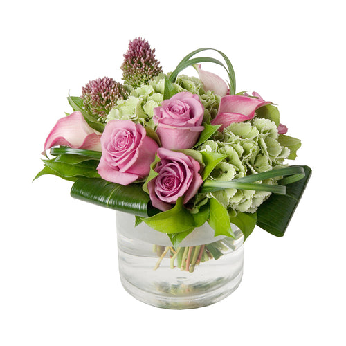 Flower arrangement featuring pink roses, green hydrangeas, pink calla lilies & allium arranged in a clear glass vase, in Flower Studio's signature style.