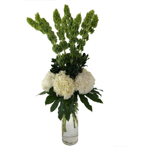Green and white flowers arranged in high style featuring white hydrangeas, green bells of ireland and lush greenery.