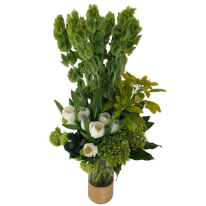 Green and white flowers arranged in high style featuring green hydrangeas, green bells of ireland, white tulips and lush greenery arranged in a gold painted vase.