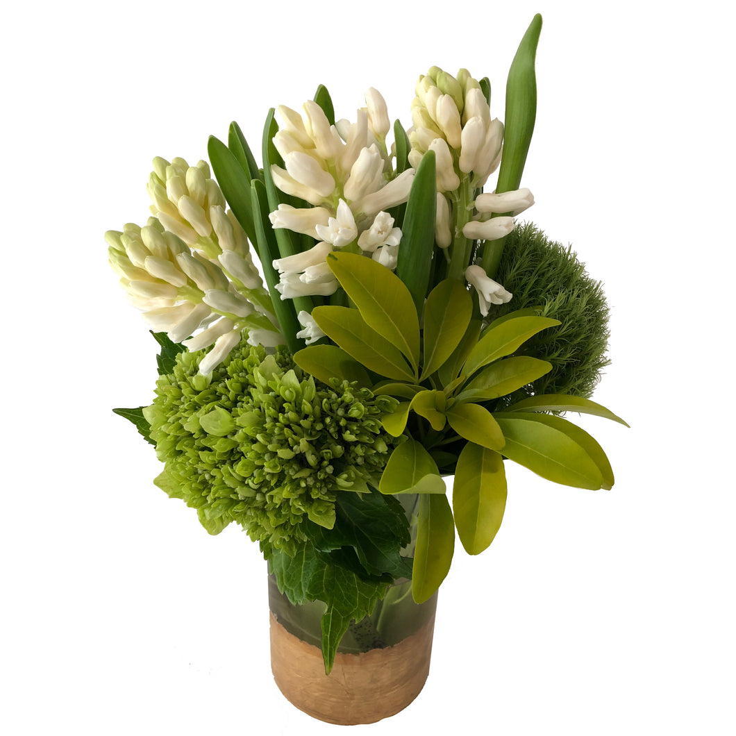 Flower arrangement with white hyacinths, green hydrangeas, and dianthus arranged in a clear glass and gold painted vase.