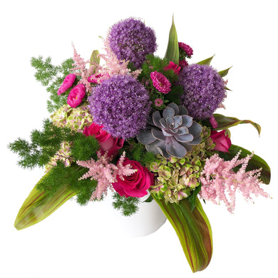Arrangement featuring purple allium, pink hydrangea, pink astilbe, pink flowers, green leaves, and succulents arranged in Flower Studio style in ceramic white vase.