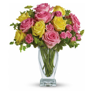 Pink and yellow roses arranged in a clear glass vase, in Flower Studio's signature style.