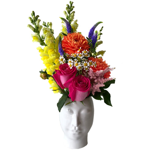 Assorted flowers featuring yellow snapdragons, pink roses, orange dahlia flowers, and purple veronica arranged in white ceramic beau head vase in Flower Studio signature style.