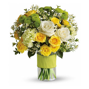 Elegant assortment of yellow roses, white roses, white carnations, green kermit mums, and waxflower arranged in a clear glass vase with green ribbon wrap, in Flower Studio's signature style.
