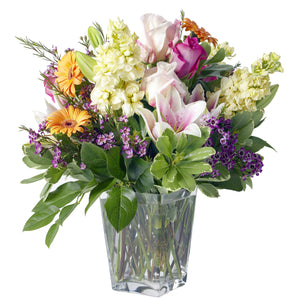 Garden arrangement featuring yellow gerbera daisies, white and pink lilies, pink roses, white stocks and purple wax flower arranged in Flower Studio signature garden style in a clear glass vase.