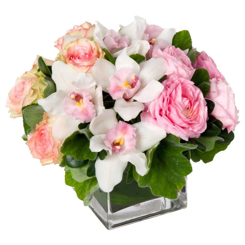 Flower arrangement featuring white cymbidium orchids, pink garden roses, and peach roses in a clear glass vase in Flower Studio's signature style.
