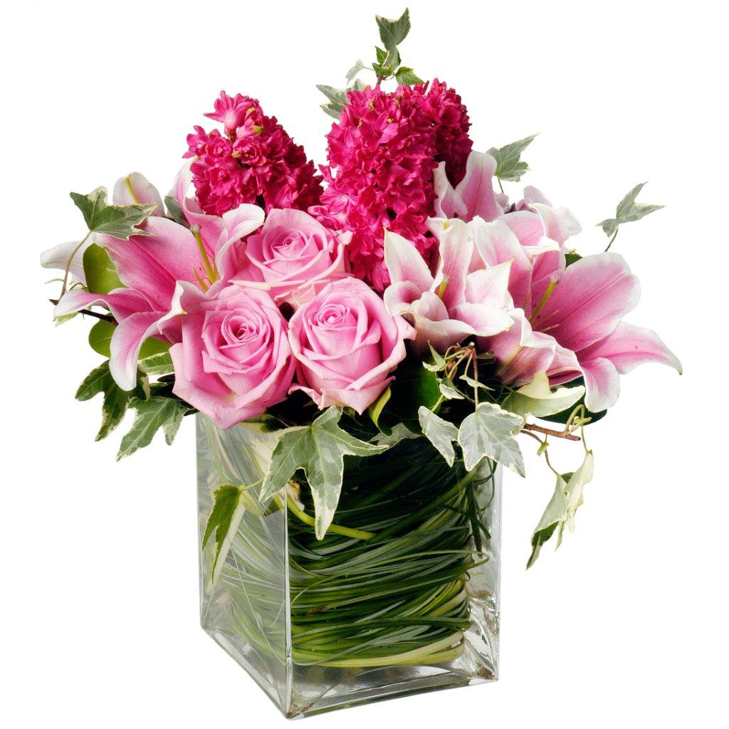 Monochromatic pink flower arrangement featuring pink roses, pink hyacinths, pink  and white lilies, and greenery in a clear glass vase with leaf wrap by Flower Studio.