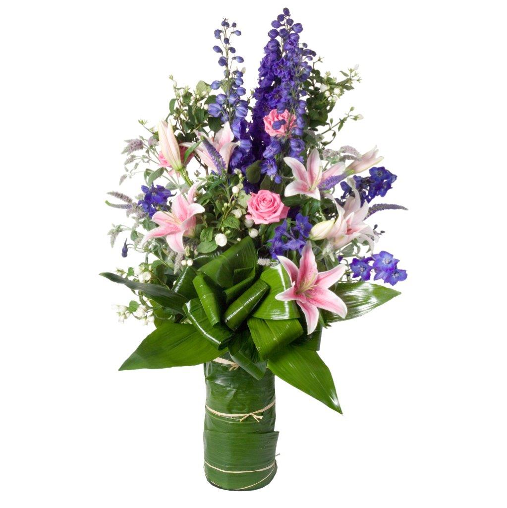 Tall flower arrangement featuring pink lilies, pink roses, purple stocks, premium greenery in a clear glass vase with green leaf wrap arranged in Flower Studio signature style.