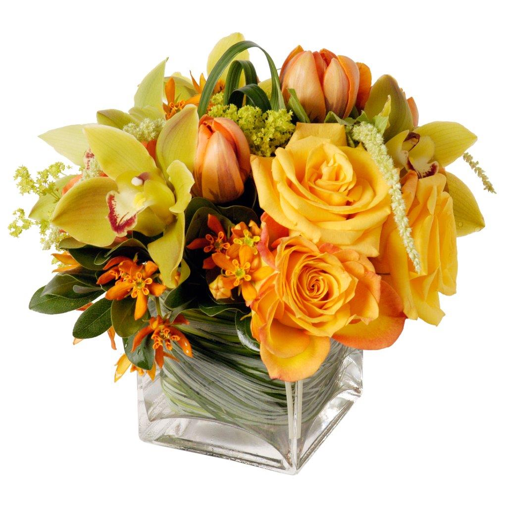 Modern flower arrangement featuring yellow roses, yellow cymbidium orchids, and orange tulips in a clear glass vase featuring greenery in Flower Studio signature style.