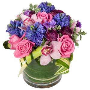 Fragrant flowers featuring pink roses, pink cymbidium orchids, purple hyacinths, and purple ranunculus in Flower Studio signature style.