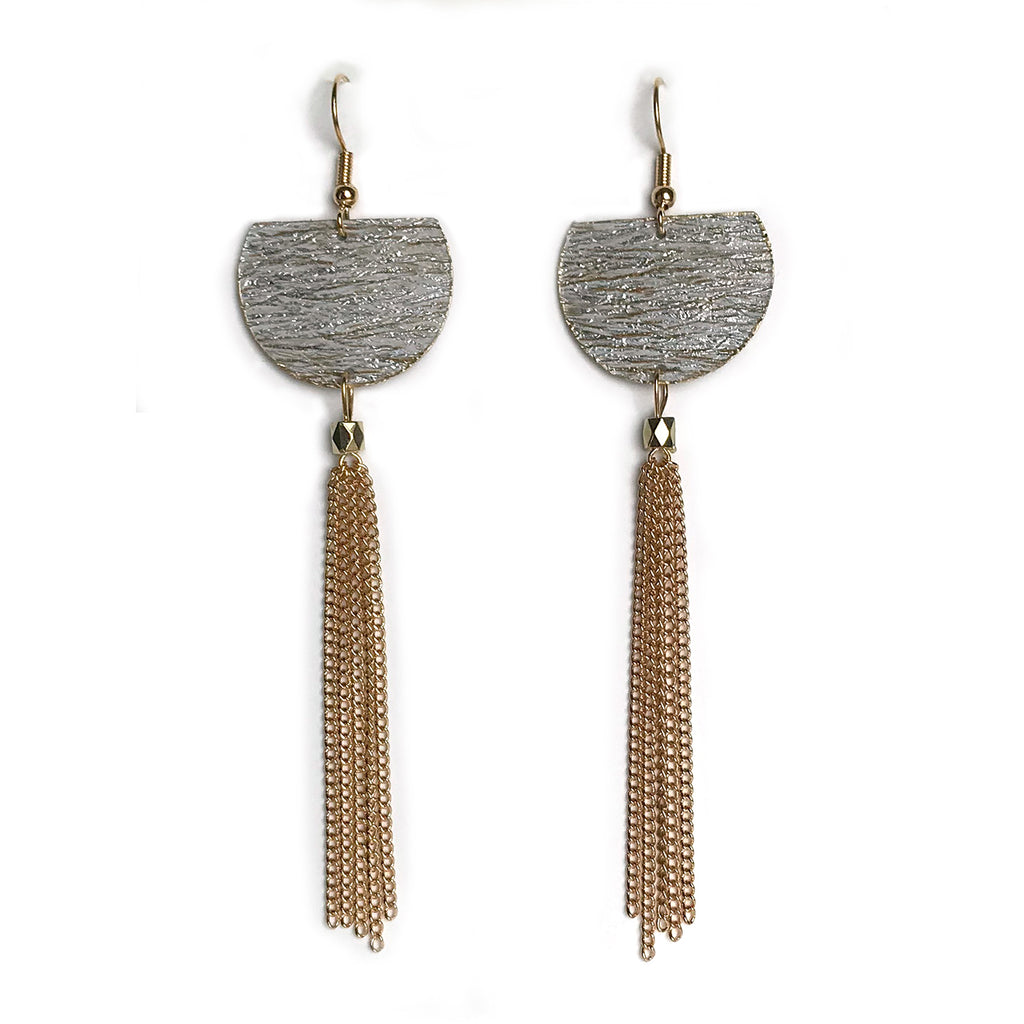 Gracie Nicole handmade jewelry. Create a little drama with these earrings made from luxurious designer wallpaper by York that has a shiny, metallic silver finish. Soft, horizontal creases create depth and texture, while whispers of golden streaks peek through. The edges are finished with gold metallic paint. Extra drama is created with long gold chain tassels.