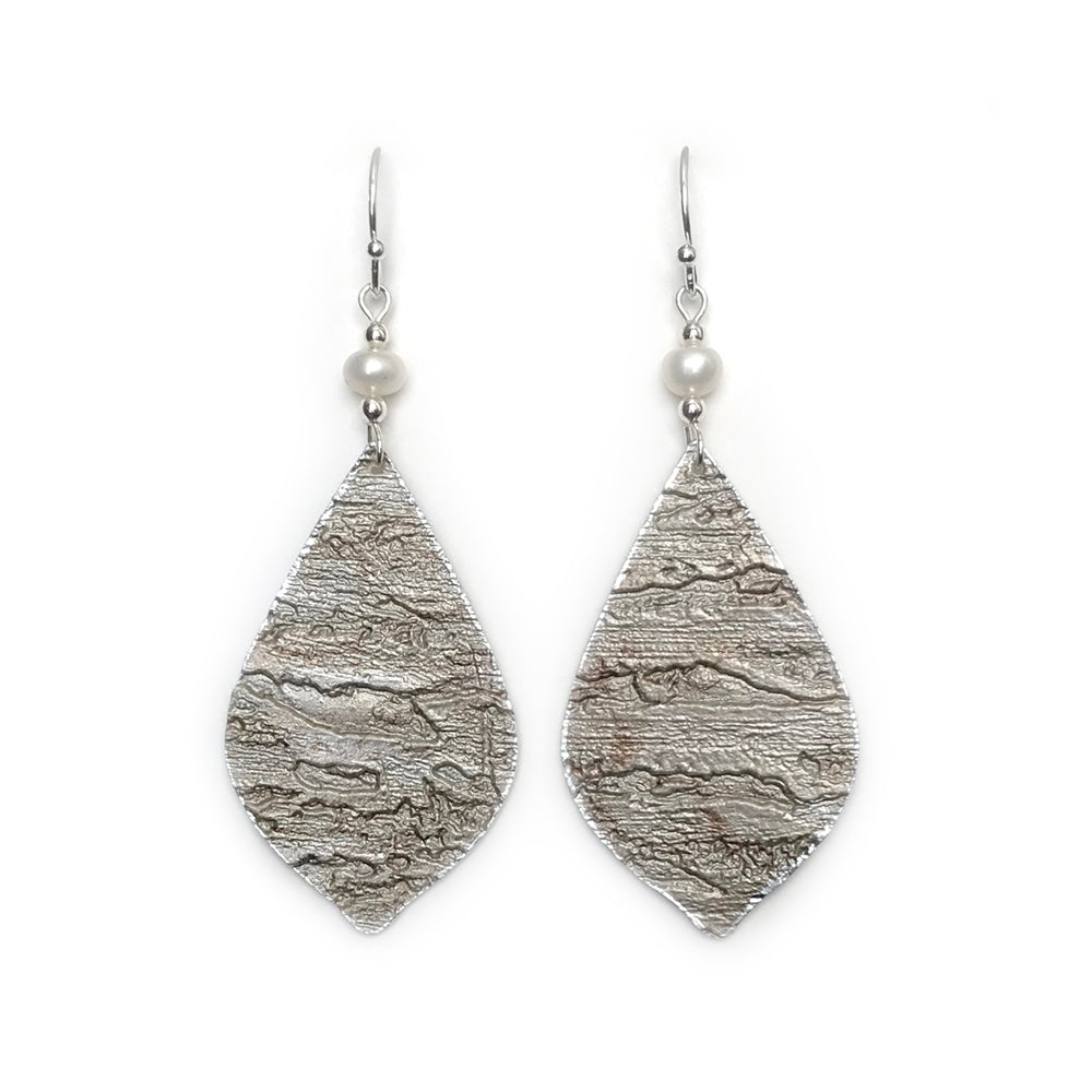 Gracie Nicole. Lightweight earrings made from textured designer wallpaper in metallic grey with subtle wisps of soft brown. The feminine leaf drop shape is topped with a pretty freshwater pearl to create an edgy yet elegant  design.